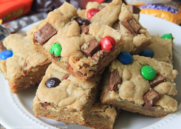 a close up of a white plate filled with Candy Bar Blondies. Each lightly colored brownie is filled with M&Ms or other candy bar pieces.
