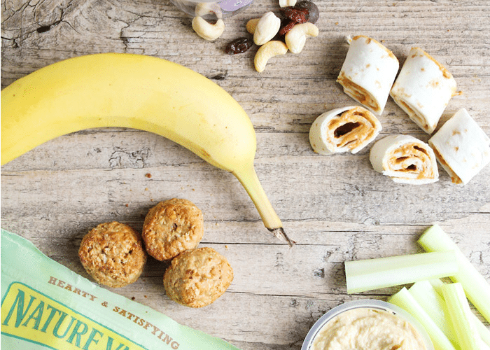 a granola bar, a banana, bite-sized pieces of a sandwich, celery sticks and nuts laying on a counter are easy snacks
