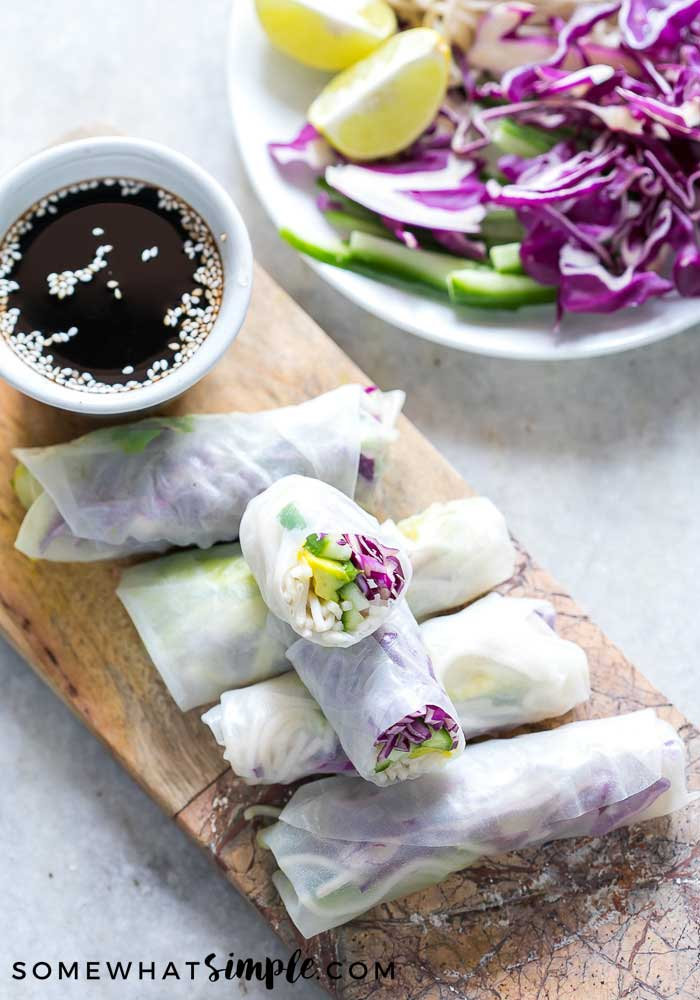 a serving tray with summer rolls and a dipping sauce
