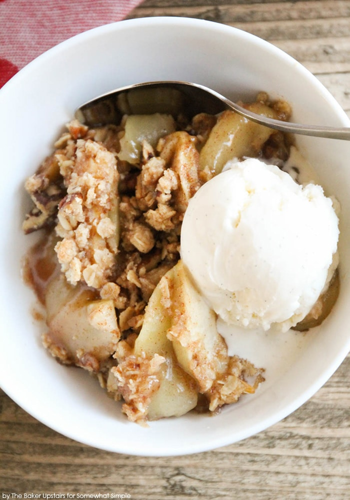 easy Apple Crisp recipe in a white bowl with a scoop of vanilla bean ice cream and a spoon.