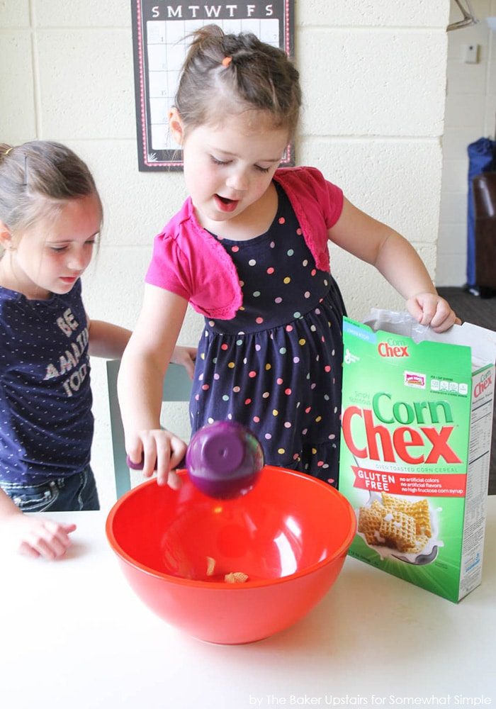 two little girls making Chex Muddy Buddies by pouring ingredients into a bowl with a box of Corn Chex next to the bowl on the counter