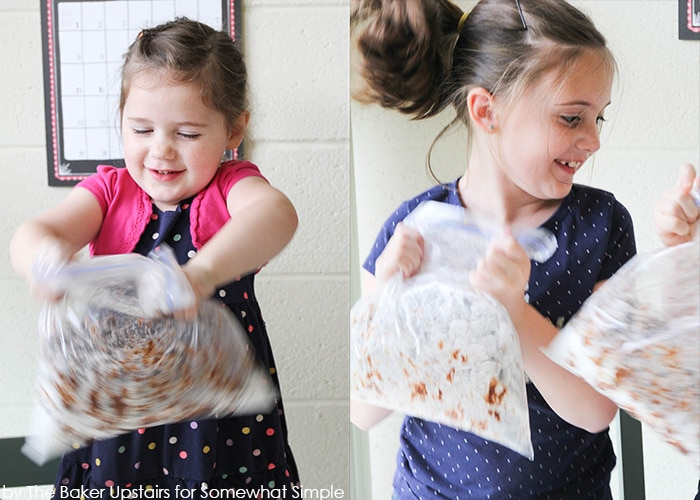 two girls shaking a big bag of Chex Muddy Buddies to thoroughly mix the ingredients for this recipe