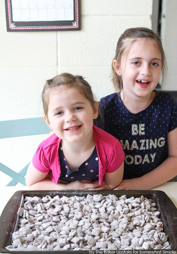 two girls with a baking sheet full of finished Chex mix Muddy Buddies covered in powdered sugar