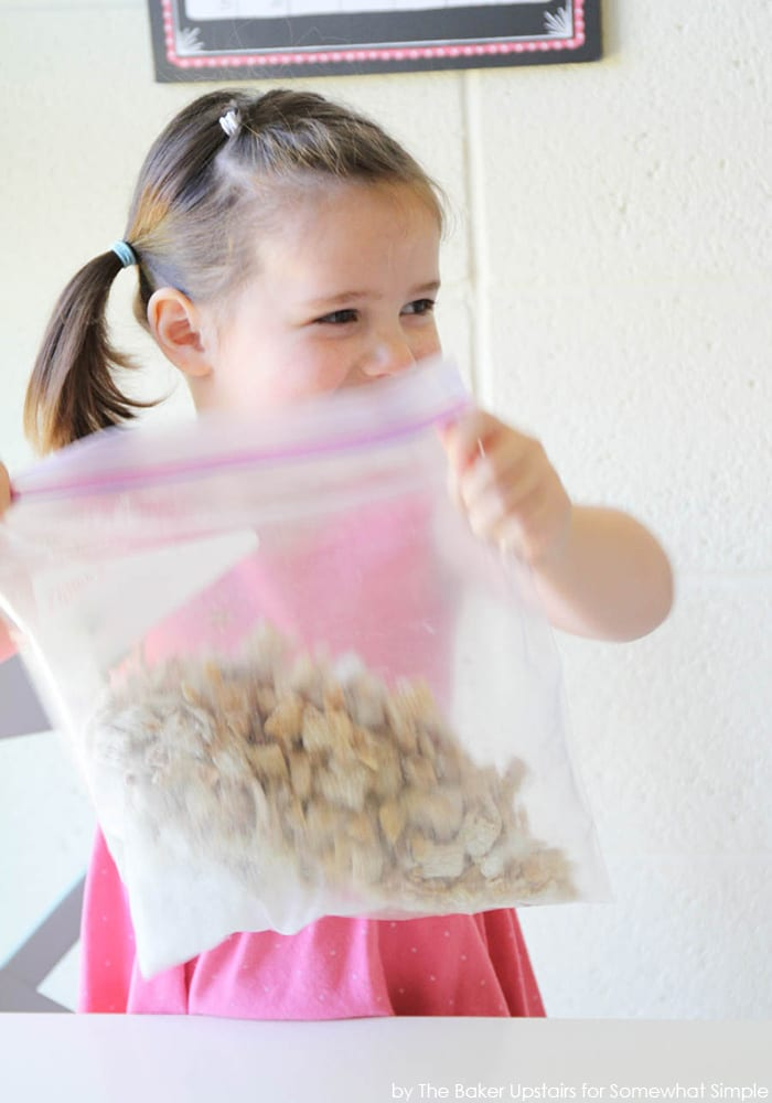 a girl shaking a bag of check mix