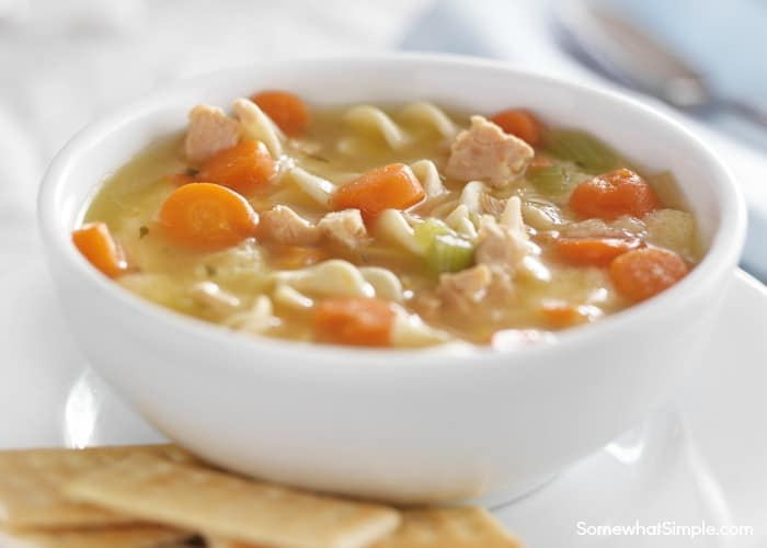 a white bowl of homemade creamy chicken noodle soup made in a crock pot using this simple recipe