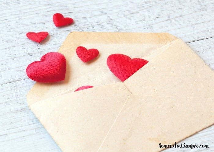 background of love letters with white wooden hearts