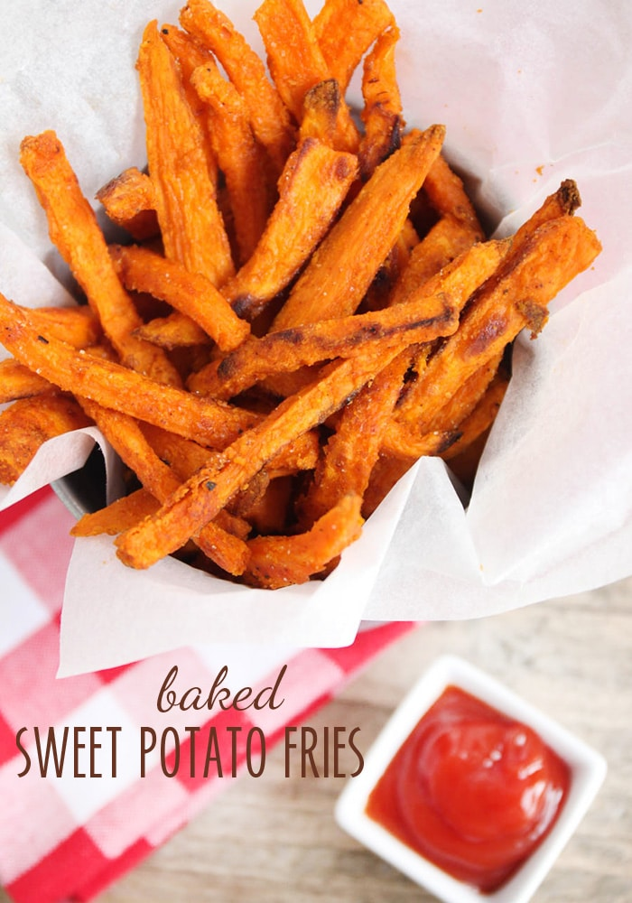 a batch of Baked Sweet Potato Fries in a metal cup with a side of ketchup on the counter next to it