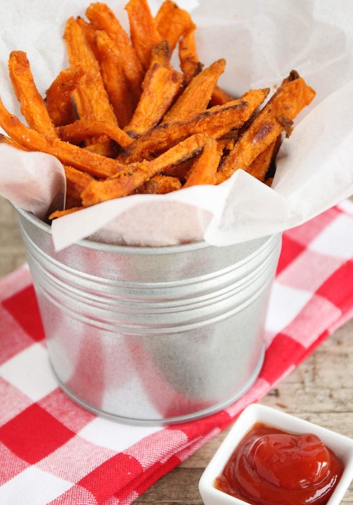a close up of a metal serving bowl of crispy Sweet Potato Fries on a red checkered napkin and a side of ketchup