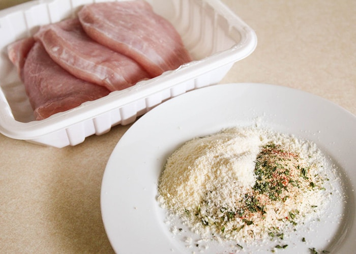 a tray of raw turkey Cutlets with a garlic and Parmesan mix on a white plate