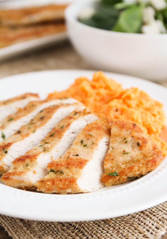 golden brown sliced Parmesan crusted Turkey Breast Cutlets on a white plate with cheesy mashed potatoes