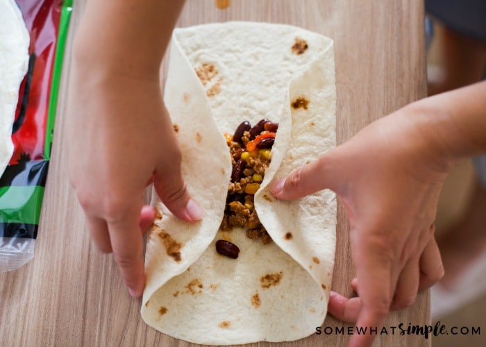 two hands rolling in the process of rolling up a tortilla with beans and rice inside to make a burrito