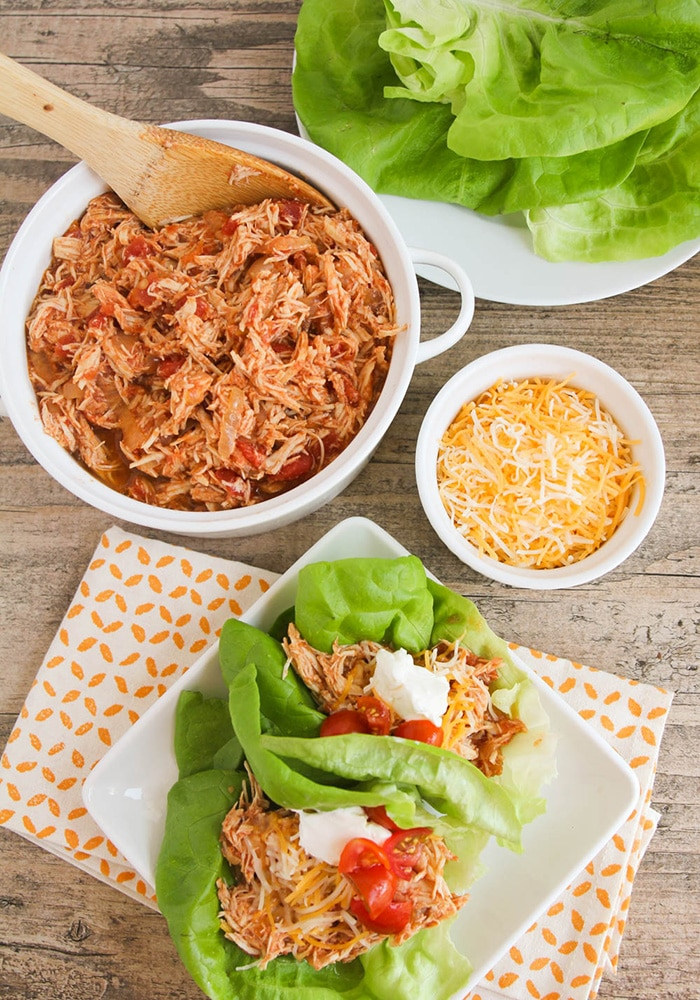Looking down on a plate with Taco Lettuce Wraps topped with sour cream, tomatoes and cheese. Next to the plate is a bowl of shredded chicken, a small bowl of cheese and a plate of lettuce leaves.