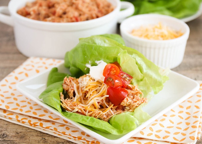 a square white plate with two Chicken Taco Lettuce Wraps on it. Each wrap is topped with shredded cheese cherry tomatoes. Behind the plate is a bowl of shredded chicken and a smaller bowl of shredded cheese.