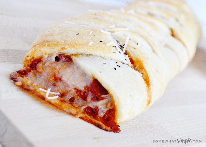 close up picture of cheese, marinara sauce and pepperoni dripping out of the end of this easy homemade calzone