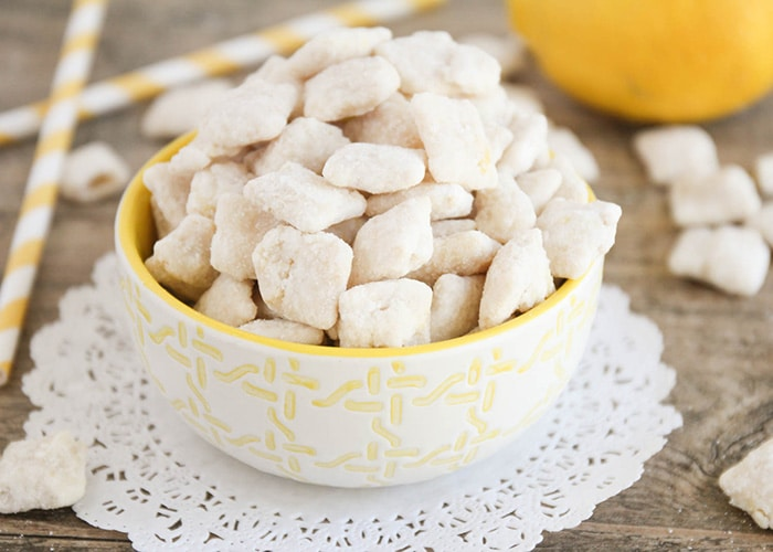 a white and yellow bowl full of lemon chex mix
