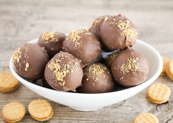 a white bowl filled with nutter butter balls covered in chocolate. Individual nutter butter cookies are scattered on the table around the bowl.