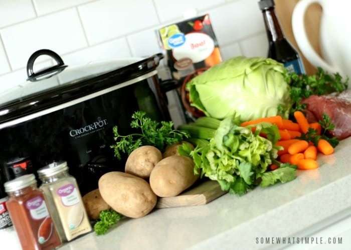 the ingredients to make corned beef and cabbage in the crock pot; potatoes, celery, cabbage, corned beef, spices and broth.
