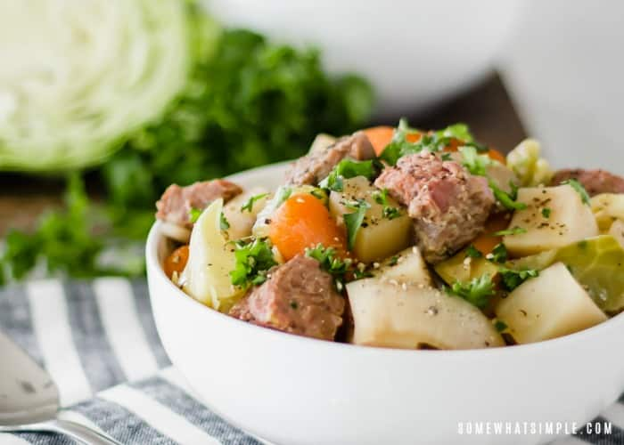 a white bowl of Corned Beef and Cabbage that was made in a slow cooker. Also, in the bowl are slices of onions, potatoes and carrots with chopped parsley on top. A half a head of cabbage is in the background.