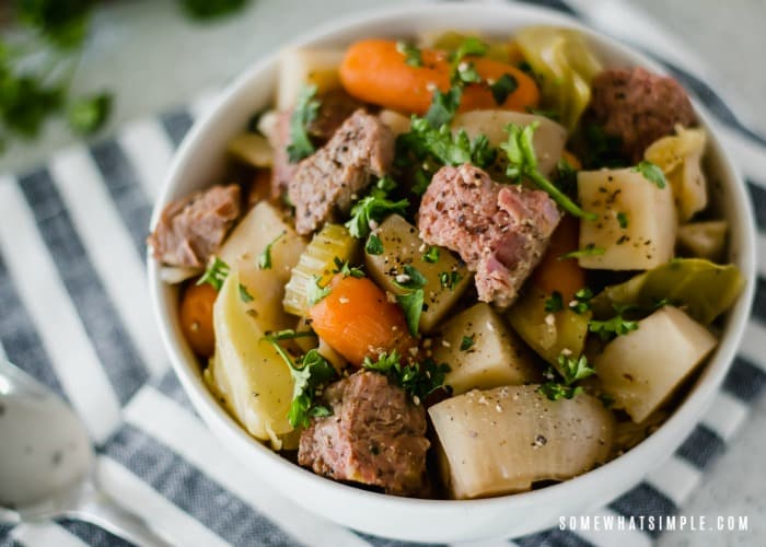 looking down on a white bowl of crock pot Corned Beef and Cabbage that is mixed with carrots celery and potatoes. The bowl is sitting on top of a black and white striped napkin.