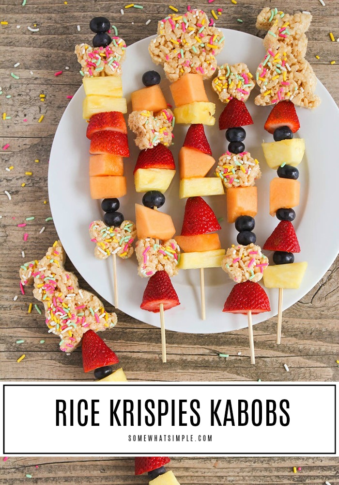 several Easter Kebabs on a white plate with one on the table next to the plate. These Easter snacks are made with rice krispies, pastel colored sprinkles, strawberries, blueberries, cantaloupe and pineapple. At the bottom of the image there's a white box with the words rice krispies kabobs written at the bottom.