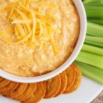 looking down on a white bowl full of this easy buffalo chicken dip recipe that was made in a crock pot and topped with shredded cheese. On the plate next to the bowl are several Ritz crackers and celery sticks