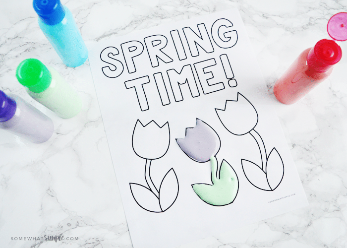 "looking down on a coloring page that says ""spring time"" with one tulip painted with homemade puffy paint and bottles of green, purple, blue and red puffy paint next to the coloring sheet"