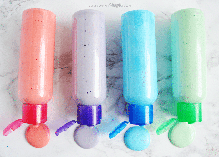 bottles of red, purple, blue and green puffy paint laying on their sides on a counter with a small puddle of puffy paint in front of them
