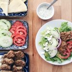 a plate filled with this easy Gyro Salad Recipe next to serving trays filled with the ingredients to make this greek salad as well as a small dish filled with tzatziki dressing