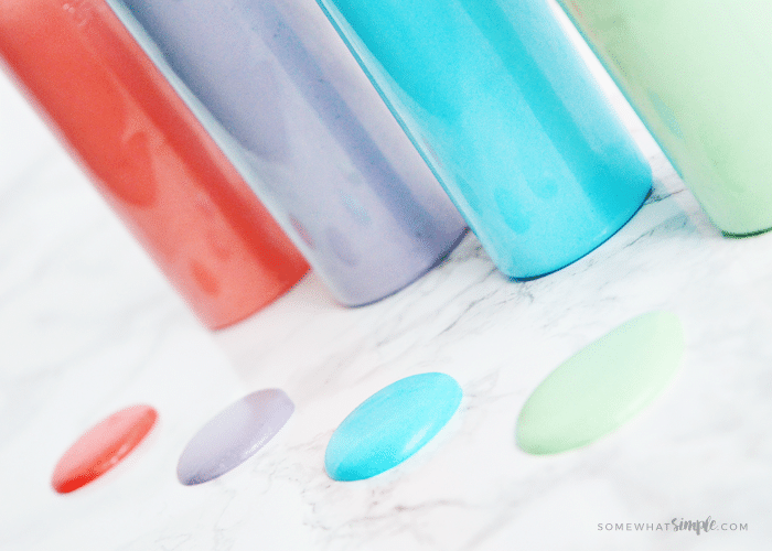 a close up of drops of red, purple, blue and green puffy paint next to bottles filled with puffy paint