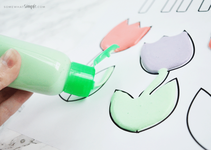 painting a portion of a tulip coloring sheet with a squeeze bottle of green puffy paint