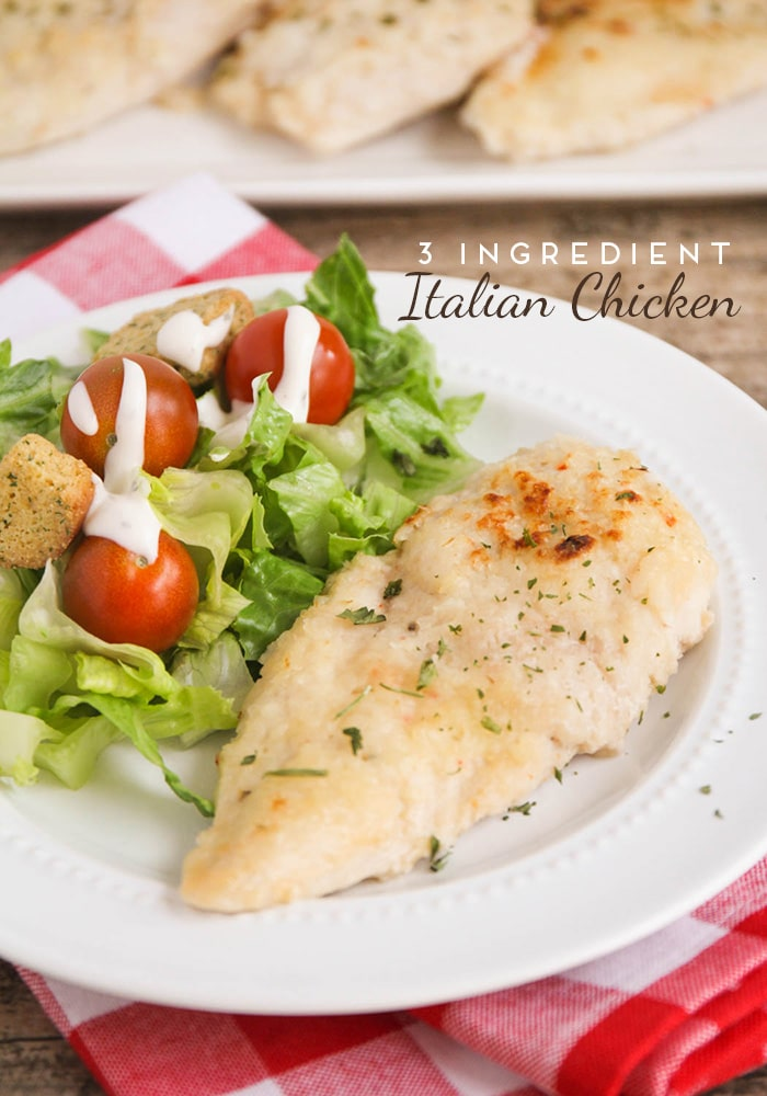 a breast of baked italian dressing chicken on a white plate with a salad on the side with ranch dressing. Additional baked italian chicken is in the background.