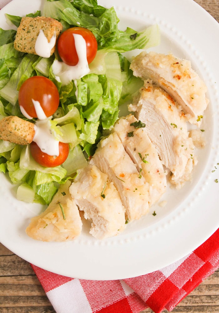 a piece of baked italian chicken made with italian dressing on a white plate with a garden salad on the side