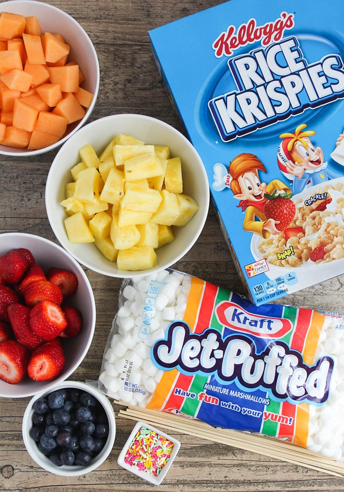 looking down on the ingredients to make these Easter Kebabs. There's a box of rice krispies, a bag of marshmallows, and bowls of cantaloupe, pineapple, strawberries and blueberries.