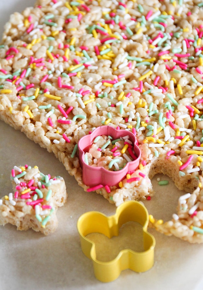 a tray of rice krispie treats covered in pastel colored sprinkles. A pink cookie cutter has be pressed down into the pan to cut out a piece in the shape of a flower.