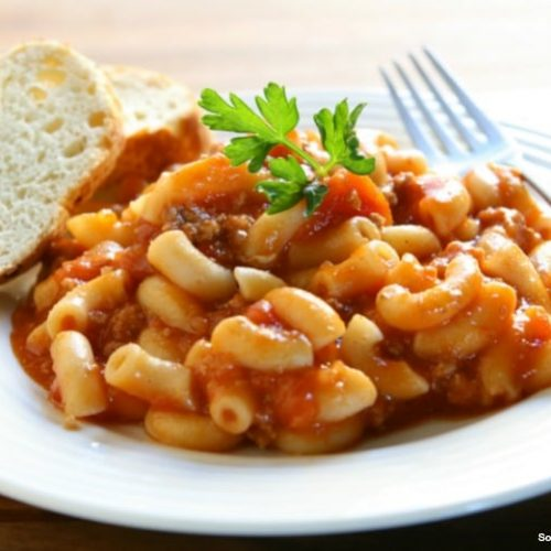 a plate of chili mac and a slice of bread