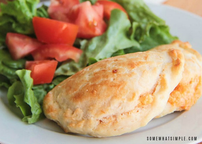 a baked chicken empanada that is golden brown on a white plate next to a green salad topped with tomatoes.
