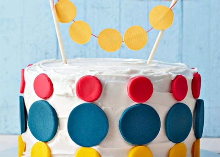 a cake with white frosting that has large red blue and yellow dots