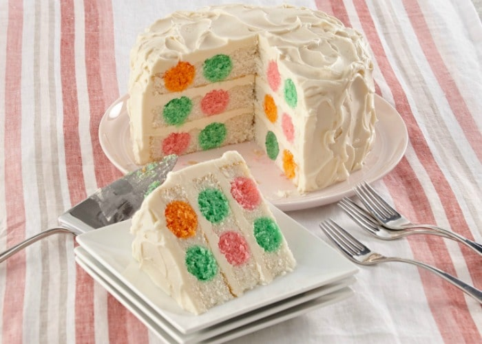 a layered vanilla cake with orange green pink and yellow polka dots with white frosting.