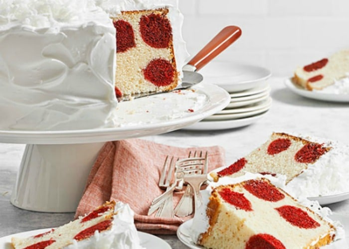 a vanilla cake with white frosting that has a few pieces cut out and are sitting on plates. The cake and the slices all have large red polka dots