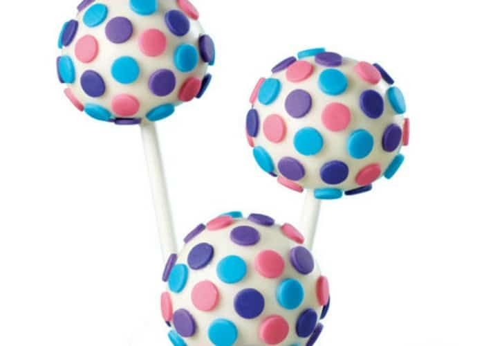 three fondant cake pops with blue and pink pastel colored polka dots