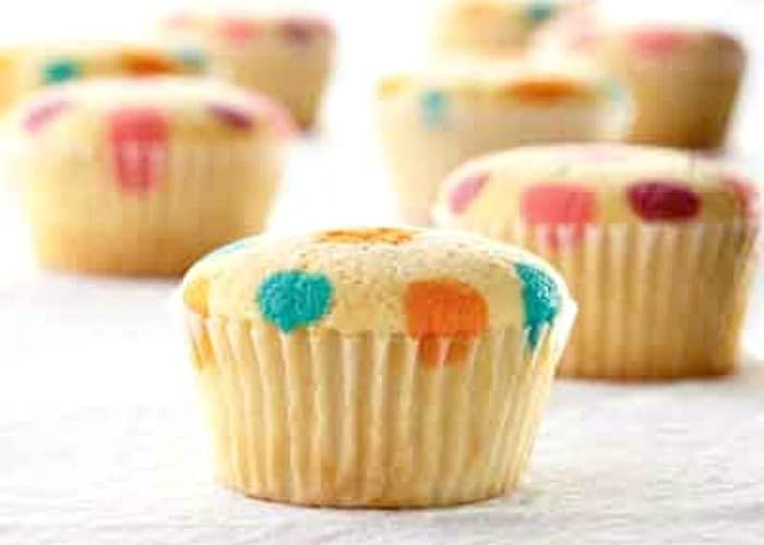 vanilla cupcakes with orange blue yellow red and purple polka dots