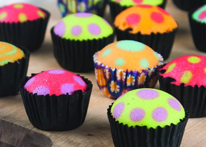 bright pastel colored cupcakes with brightly colored polka dots and black liners