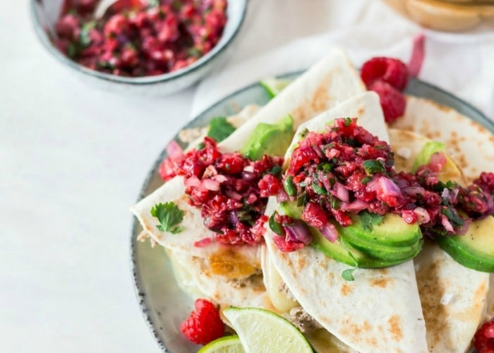 a plate piled high with slices of quesadillas topped with a raspberry salsa and slices of avocado