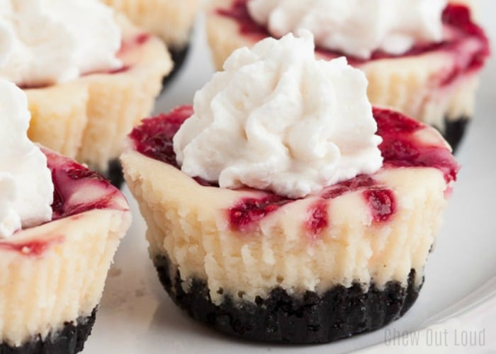 a close up of raspberry cheesecake bites topped with whipped cream