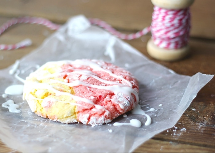 a Strawberry Lemonade Cookie on a square of parchment paper with icing drizzled over the top