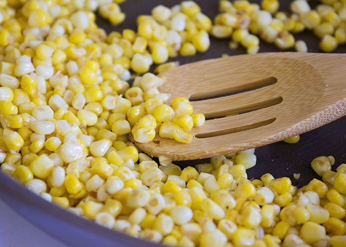 kernels of corn cooking in a frying pan