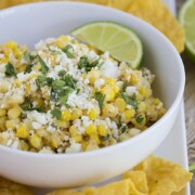 a bowl of Mexican corn salad topped with cilantro and cotija cheese on a serving dish next to tortilla chips