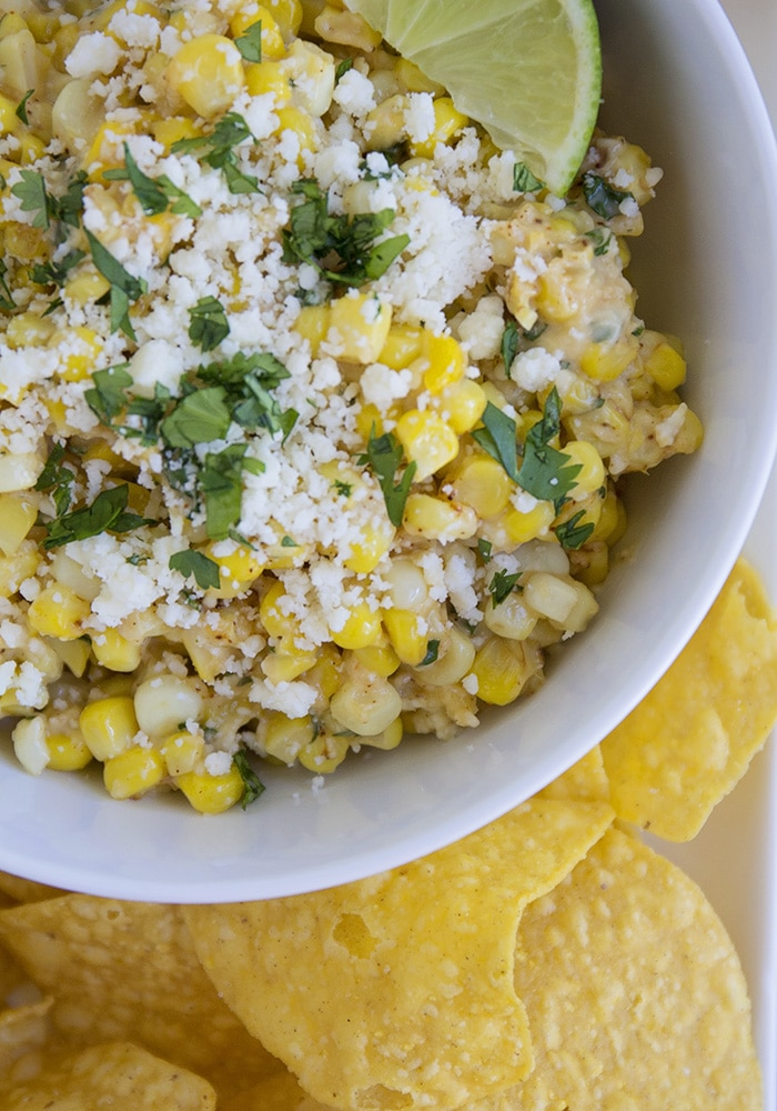 looking down on a bowl of Mexican Corn Salad with a slice of lime on top