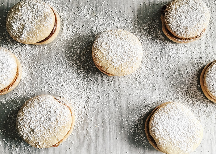 alfajores with powdered sugar on a table made using this recipe