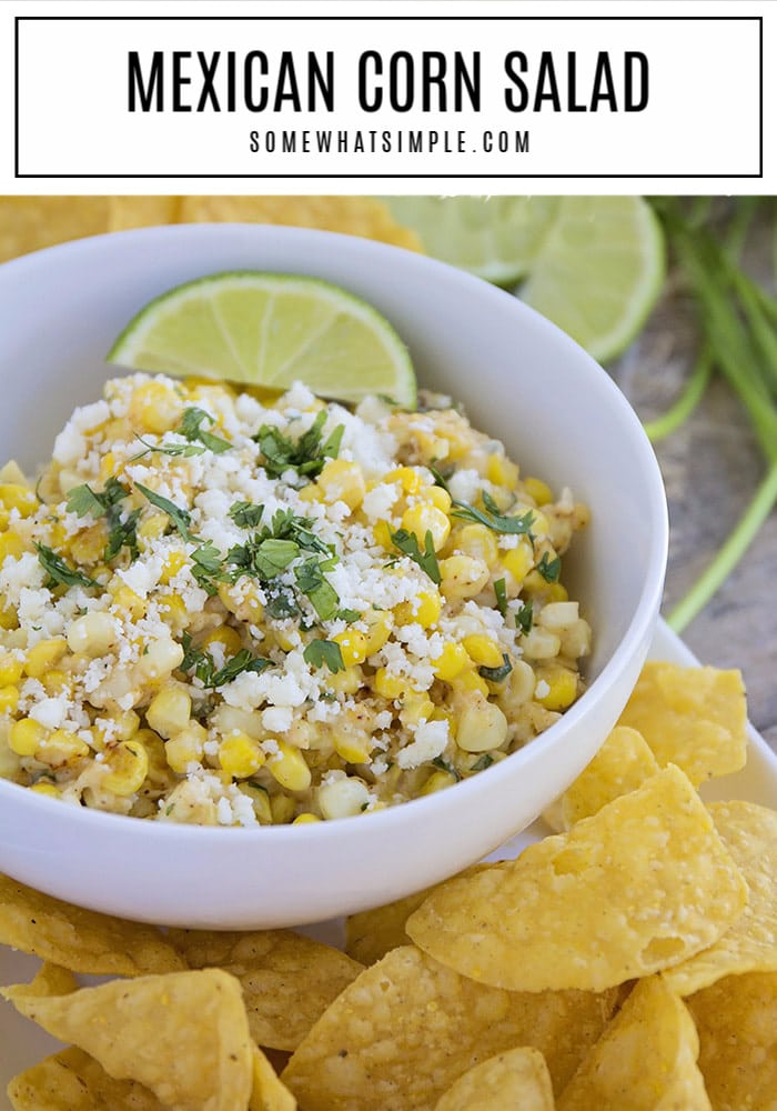 a bowl of mexican corn salad topped with a slice of lime, cheese and cilantro next to a side of chips